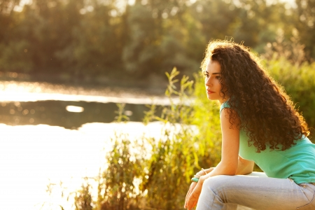 curly hair woman: young curly hair woman enjoy in summer sun at lake Stock Photo