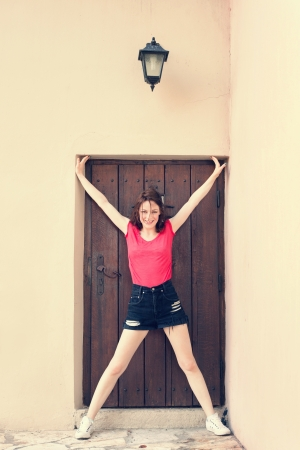 smiling girl stand with open arms and legs in doorframe of old wooden door  in front old house, lantern above door photo