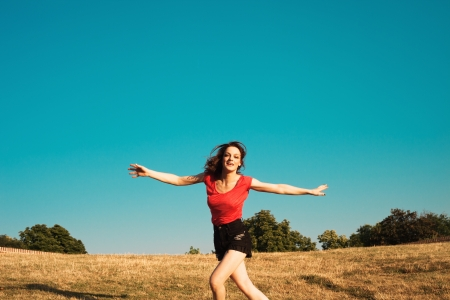 smiling girl in shorts and t-shirt run with open arms on the hill,  summer hot day, blue sky in background and dry grass Stock Photo - 14450581