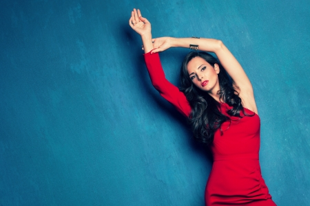 beautiful elegant woman in red dress on blue wall studio shot photo