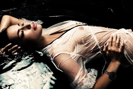 젖은: 검은 물에 젖은 흰색 셔츠에 관능적 인 여자 스톡 사진