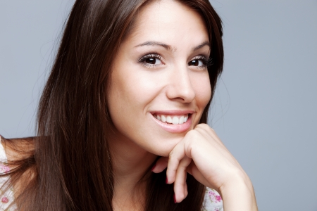 friendly smiling young woman portrait hand lean on chin,  studio shot photo