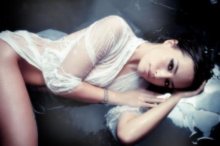sinnlich schöne Frau in weißem Hemd nass ruht in Wasser