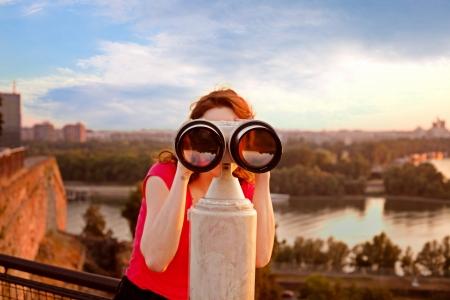 Frau sucht durch Besichtigungen Fernglas auf Belgrader Festung Himmel, Fluss und die Stadt im Hintergrund