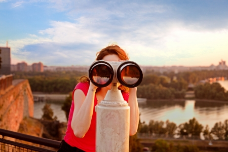 looking at viewer: woman looking through sightseeing  binoculars on Belgrade Fortress sky, river and city in background