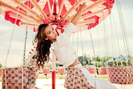 junge Frau im Vergnügungspark auf dem Karussell im Sommer sonnigen Tag