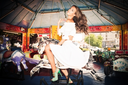 full body shot: young woman in white summer dress on merry go round in children amusement park summer day
