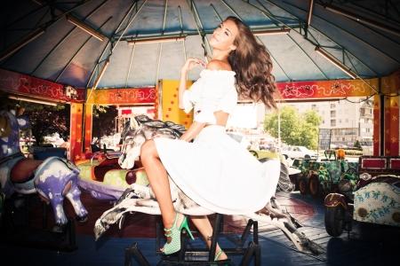 merry go round: young woman in white summer dress on merry go round in children amusement park summer day