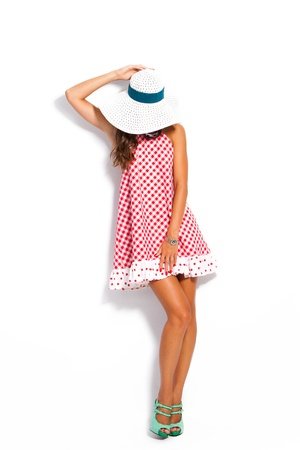 young fashion model in summer dress, hat and high heel shoes studio white photo