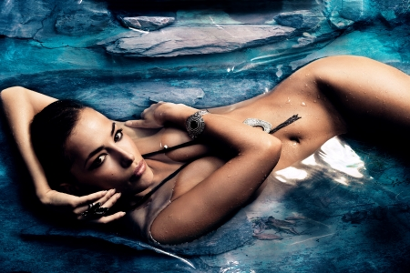 tanned:  sensual nude woman enjoy in natural pool of blue stone