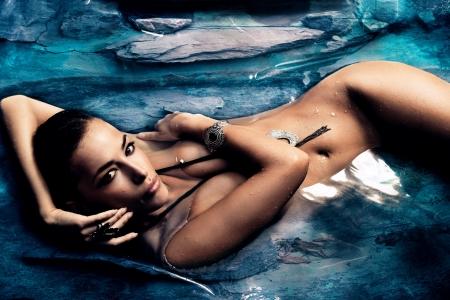 sinnliche nackte Frau genießen im natürlichen Pool des blauen Stein Lizenzfreie Bilder