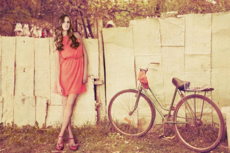 young fashion girl  stand by old-fashioned bicycle in the village retro colors texture added photo