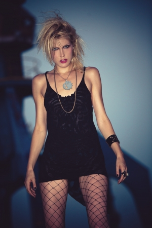 aggressive people: blond fashion model in short black dress,  mesh stockings and punk hairstyle outdoor shot at dusk Stock Photo
