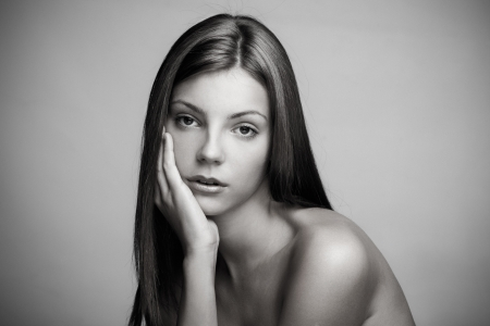 natural beauty portrait of a young woman with long straight hair with hand on chin in black and white studio shot small amount of grain added photo