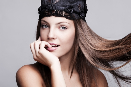 young brunette woman with smooth silky hair in motion wearing satin cap studio shot photo