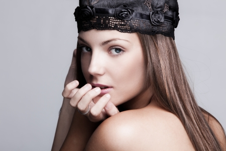 young woman beauty portrait wearing satin cap with embroidery photo