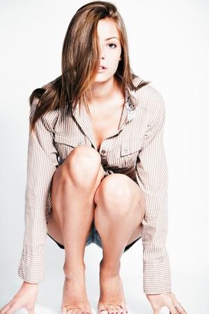 young barefoot fashion model in shirt studio shot photo