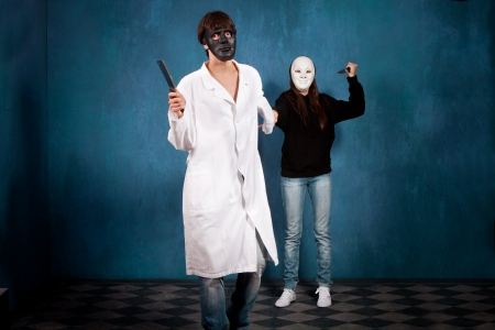teen couple with halloween masks and knifes in blue room  Stock Photo - 15119125