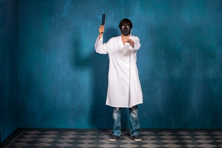 scary man: man with black scary mask and meat chopper wearing white coat in blue room full body shot