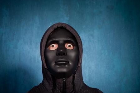 ocas: hombre con máscara de miedo negro del estudio tiro Foto de archivo