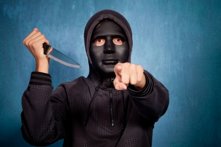 scary man: man with black scary mask and big knife point with finger