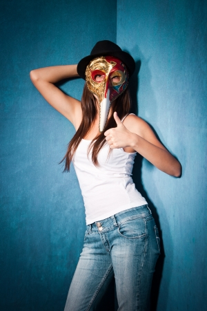 teen girl wearing Venetian mask,black hat and blue jeans stand in corner of room with thumb up Stock Photo - 15119061