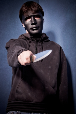 man with black scary mask hold knife in front of him studio shot photo