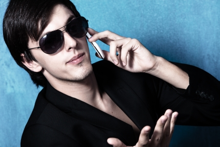 suspicious: young suspicious businessman with cell phone black suite and sunglasses