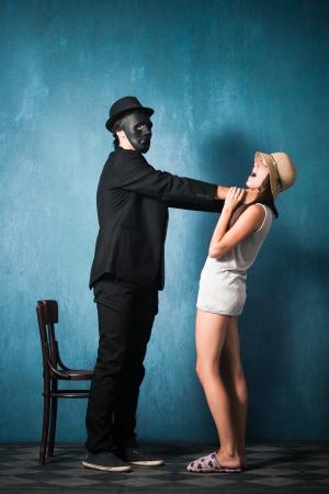 to strangle: man with black mask strangle  young girl studio shot Stock Photo
