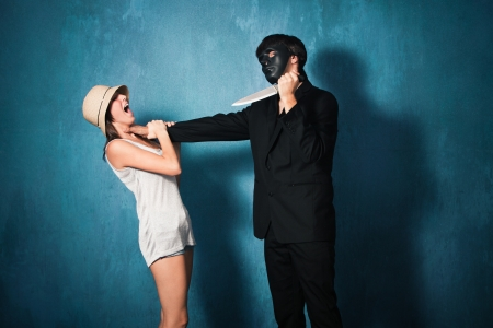 madman: man with black mask attack young girl with knife studio shot