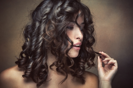 sensual brunette woman with shiny curly silky hair studio shot photo