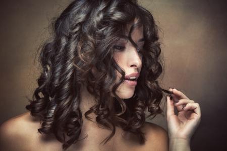 sinnliche Brünette Frau mit glänzenden curly seidiges Haar studio shot