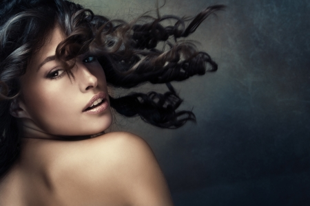 wild hair: beautiful exotic tanned woman with long wavy hair in motion studio shot darker tones