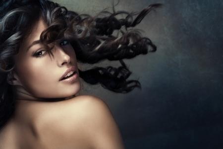 schöne exotische gebräunte Frau mit langem, welligem Haar in Bewegung studio shot dunklere Töne