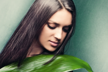 beauty woman portrait with leaf looking down studio shot horizontal