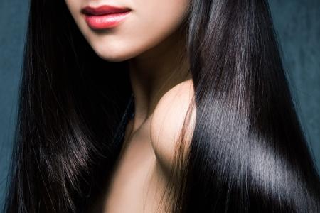 Frau mit langen glänzenden schwarzen Haaren und roten Lippen studio shot