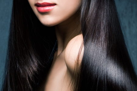 woman with long shiny black hair and red lips studio shot photo