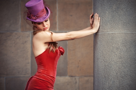 young elegant woman in red dress and cylinder  leaning against column photo
