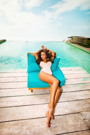 sunbathing: attractive young woman in swimwear by the pool
