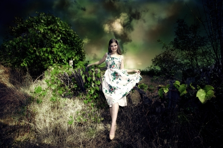 fairy woman: smiling young woman fairy like in elegant dress in dark green environment Stock Photo