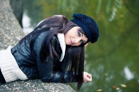 smiling young woman in autumn casual clothes portrait by the lake photo