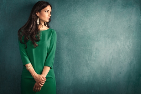 lean: elegant mature woman in green dress lean on wall  Stock Photo