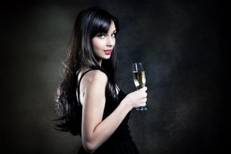 seductive women: smiling beautiful elegant young woman with glass of champagne studio shot Stock Photo