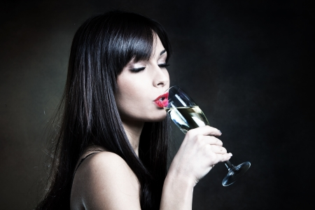 young woman drinking champagne studio shot photo