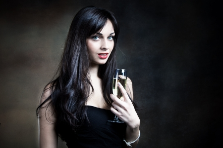 attractive young woman in elegant dress and glass of champagne photo