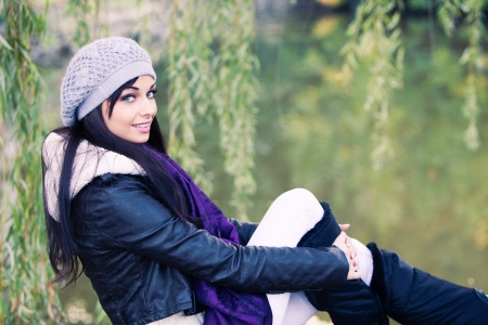 black hair blue eyes: smiling young woman in autumn casual clothes portrait by the lake Stock Photo