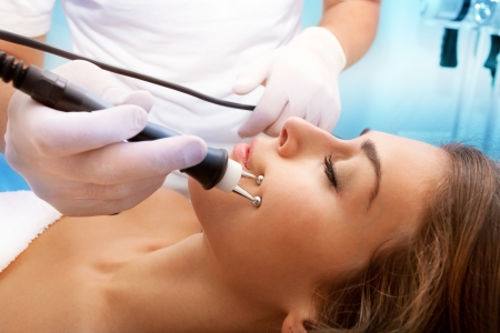 beauty therapist: woman face treatment in medical spa center