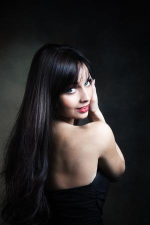 black hair blue eyes: smiling blue eyes woman with long black hair portrait studio dark background