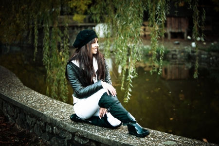 smiling young woman in winter clothes outdoor portrait by pond  photo