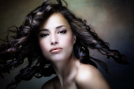 sensual brunette woman with shiny curly silky hair in motion studio shot